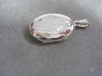 Ovaal bewerkt zilveren medaillon 35 x 25 mm.